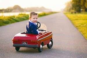 small boy in a red toy car at sunset | Basic Auto Safety Tips For Parents