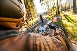 Man seat on the motorcycle on the forest road | May Is Motorcycle Awareness Month