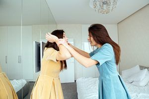 Two mad irritated young sisters twins standing and arguing in bedroom   Suing a Family Member for Personal Injury