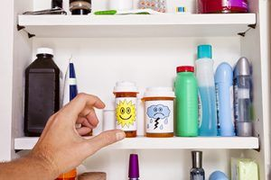 A male left hand reaches into a medicine cabinet for a pill container.