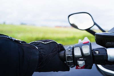 Riding motorcycle, close-up of hand on handlebar | Left Turn Motorcycle Accident Collisions