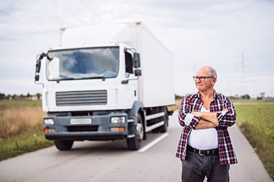 Handsome senior man posing next to his trunk with crossed arms | Truck Driver Health and Accident Risk