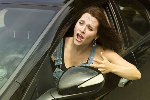 young woman sitting in car leaning out window screaming in anger | https://paysingerlaw.com/most-of-us-have-been-guilty-of-aggressive-driving/