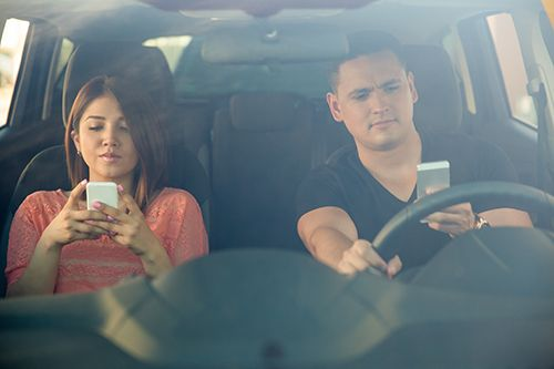 Portrait of a young couple texting and driving together, as seen through the windshield | Dangerous Driving Habits