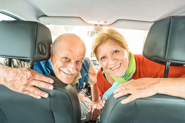 smiling senior couple looking back from front seat of car | Older Drivers Aren't Talking About Their Declining Driving Ability
