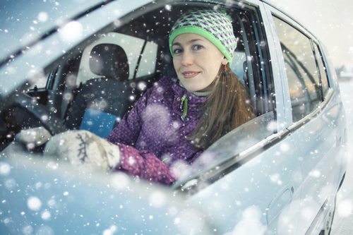 woman driving car in snow, looking out the car window | Colorado winter driving tips