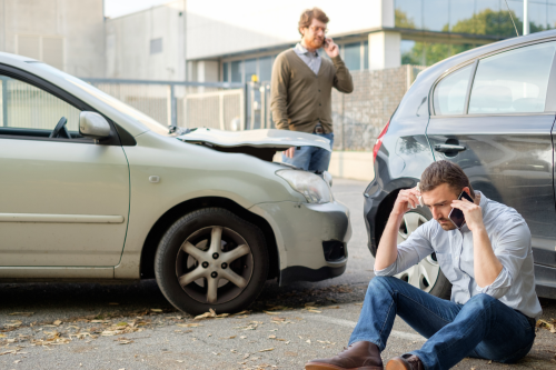 two men engaged in a car accident | call the insurance company after a car accident