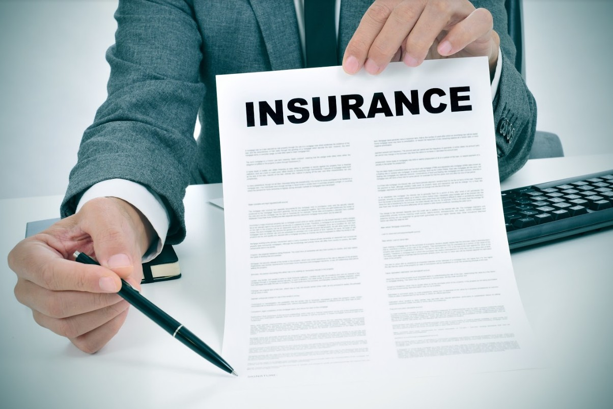 insurance agent handing out insurance policy | tips to survive an insurance dispute after a car accident