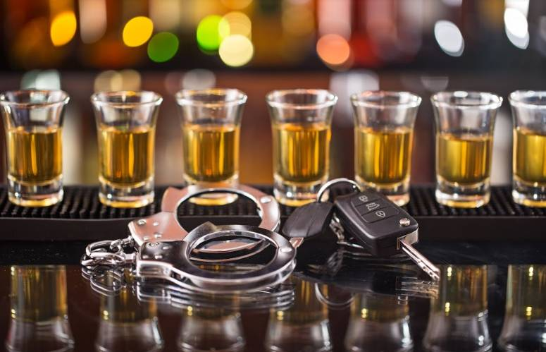 alcohol in shot glasses with handcuffs and car keys in front | drunk driving statistics in the united states