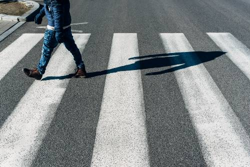 Teenager in blue jacket crosses the pedestrian lane | school zone distractions